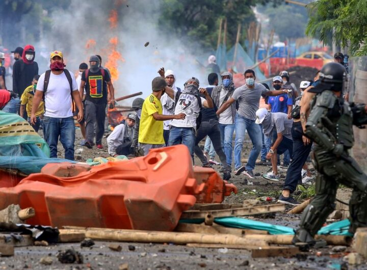 Demonstrators clash with riot police during a protest against a tax reform bill launched by Colombian President Ivan Duque, in Cali, Colombia on April 29, 2021. - Workers' unions, teachers, civil organizations, indigenous people and other sectors reject the project that is underway in the Congress, considering that it punishes the middle class and is inappropriate in the midst of the crisis unleashed by the COVID-19 pandemic. (Photo by Paola MAFLA / AFP) (Photo by PAOLA MAFLA/AFP via Getty Images)